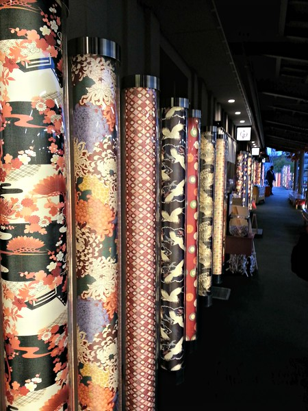 "Downtown Arashiyama has ""kimono forests"" like this. They go well with the purple train."