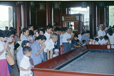 A group of people praying to the gods at a typical, larger shrine in Tokyo.  They will step up to the front, each clap their hands twice to summon the gods, then toss some coins into the large hopper in front.  '65-'66