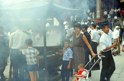 Mom and boys absorbing holy incense smoke which will improve intelligence.  That is why the site is always surrounded by Japanese school pupils, especially  during testing time!  Asaska Shrine, Tokyo.  '65-'66