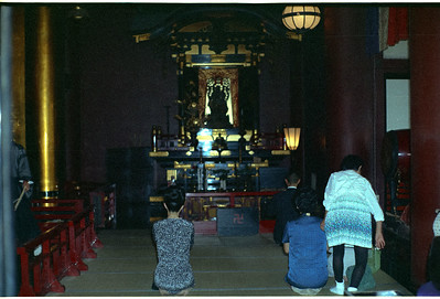A group of people praying inside a neighborhood Tokyo Shrine. '65-'66