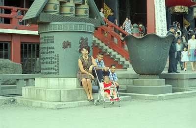 Martha and boys at entrance to Asaska Shrine in Tokyo.  The stacked wooden kegs on the monument at barrels of Saki rice wine as offerings to the Japanese Deity. '65-'66