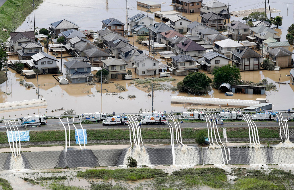 . Water is drained from partly submerged residential area following heavy rain in Kurashiki, Okayama prefecture, southwestern Japan, Sunday, July 8, 2018. Heavy rainfall hammered southern Japan for the third day, prompting new disaster warnings on Kyushu and Shikoku islands Sunday. (Koji Harada/Kyodo News via AP)