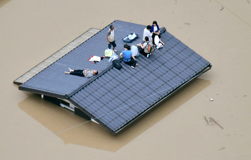 . People waif to be rescued on the top of a house almost submerged in floodwaters caused by heavy rains in Kurashiki, Okayama prefecture, southwestern Japan, Saturday, July 7, 2018. Torrents of rainfall and flooding continued to batter southwestern Japan. (Shingo Nishizume/Kyodo News via AP)