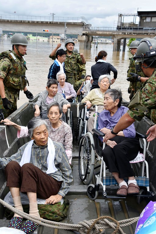. Elderly people are rescued on boat as the city is flooded following heavy rain in Kurashiki city, Okayama prefecture, southwestern Japan, Sunday, July 8, 2018. Heavy rainfall hammered southern Japan for the third day, prompting new disaster warnings on Kyushu and Shikoku islands on Sunday. (Kyodo News via AP)