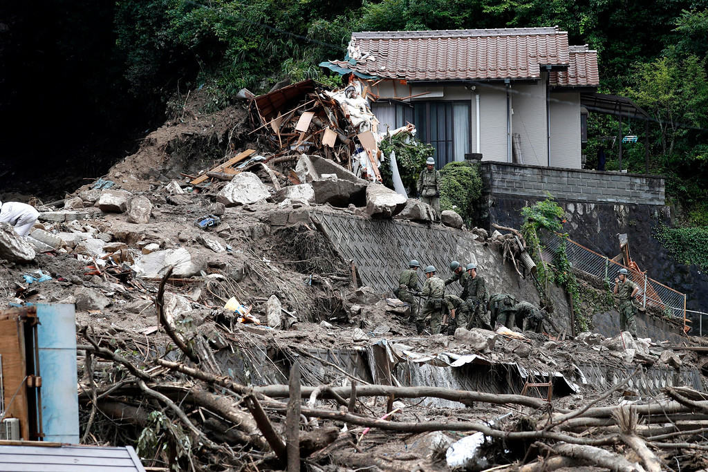 . Rescuers make search operation in a landslide site following heavy rain in Higashi Hiroshima city, Hiroshima prefecture, southwestern Japan, Sunday, July 8, 2018. Heavy rainfall hammered southern Japan for the third day, prompting new disaster warnings on Kyushu and Shikoku islands Sunday. (Koji Harada/Kyodo News via AP)