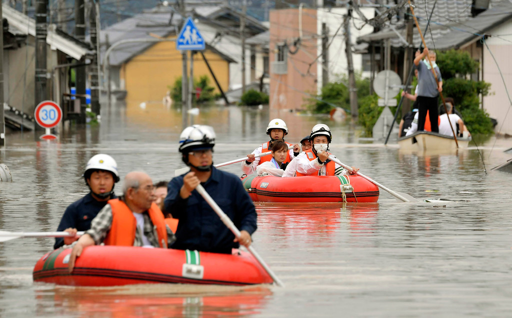 . Residents are rescued by boat in Kurashiki, Okayama prefecture, western Japan Saturday, July 7, 2018. Torrents of rainfall and flooding battered a widespread area in southwestern Japan on Saturday, with local media casualty reports climbing quickly. (Kyodo News via AP)
