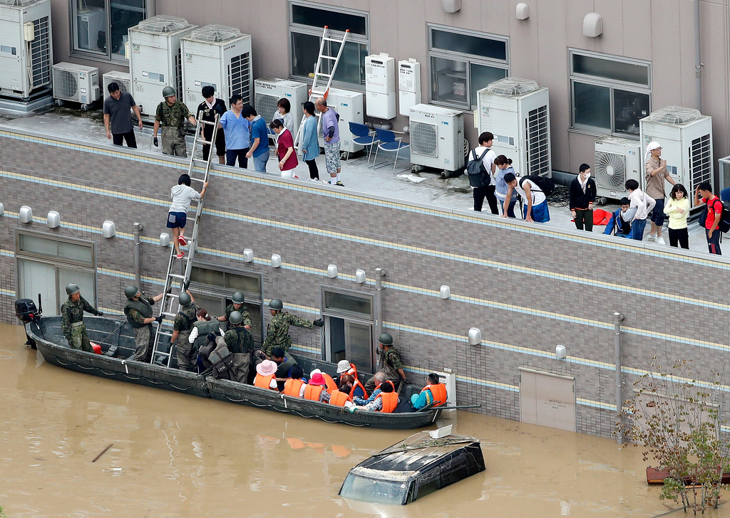. People who are stranded at a flooded hospital are rescued following heavy rain in Kurashiki city, Okayama prefecture, southwestern Japan, Sunday, July 8, 2018. Heavy rainfall hammered southern Japan for the third day, prompting new disaster warnings on Kyushu and Shikoku islands on Sunday. (Shohei Miyano/Kyodo News via AP)