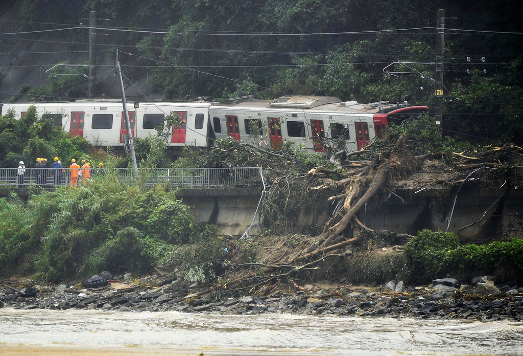 . A train remains derailed by a landslide caused by heave rains in Karatsu, Saga prefecture, southwestern Japan, Saturday, July 7, 2018. Torrents of rainfall and flooding continued to batter southwestern Japan. (Tsuyoshi Ueda/Kyodo News via AP)