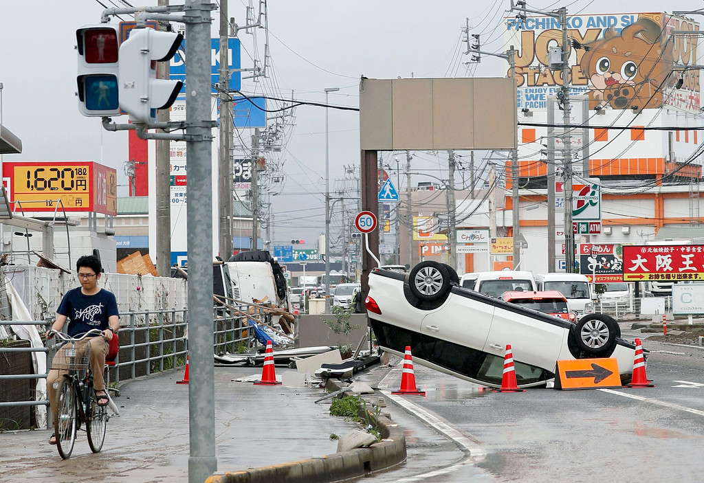 . An overturned car is seen on a road following heavy rain in Ozu city, Ehime prefecture, southwestern Japan, Sunday, July 8, 2018. Heavy rainfall hammered southern Japan for the third day, prompting new disaster warnings on Kyushu and Shikoku islands on Sunday. (Michi Ono/Kyodo News via AP)