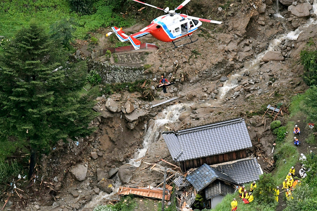 . A rescue helicopter hovers over damaged buildings after a landslide caused by heavy rains in Iwakuni, Yamaguchi prefecture, southwestern Japan, Saturday, July 7, 2018. Torrents of rainfall and flooding continued to batter southwestern Japan. (Kyodo News via AP)