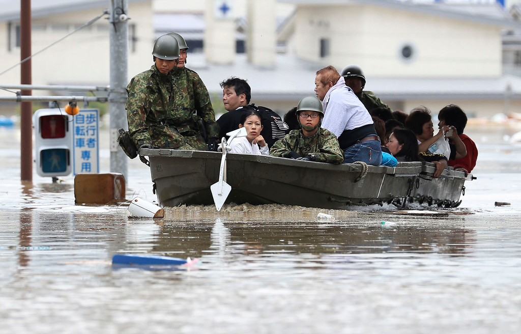 . Japan Ground Self-Defense Force members use a boat to evacuate residents from a flooded area caused by heavy rains in Kurashiki, Okayama prefecture, southwestern Japan, Saturday, July 7, 2018. Torrents of rainfall and flooding continued to batter southwestern Japan. (Takumi Sato/Kyodo News via AP)
