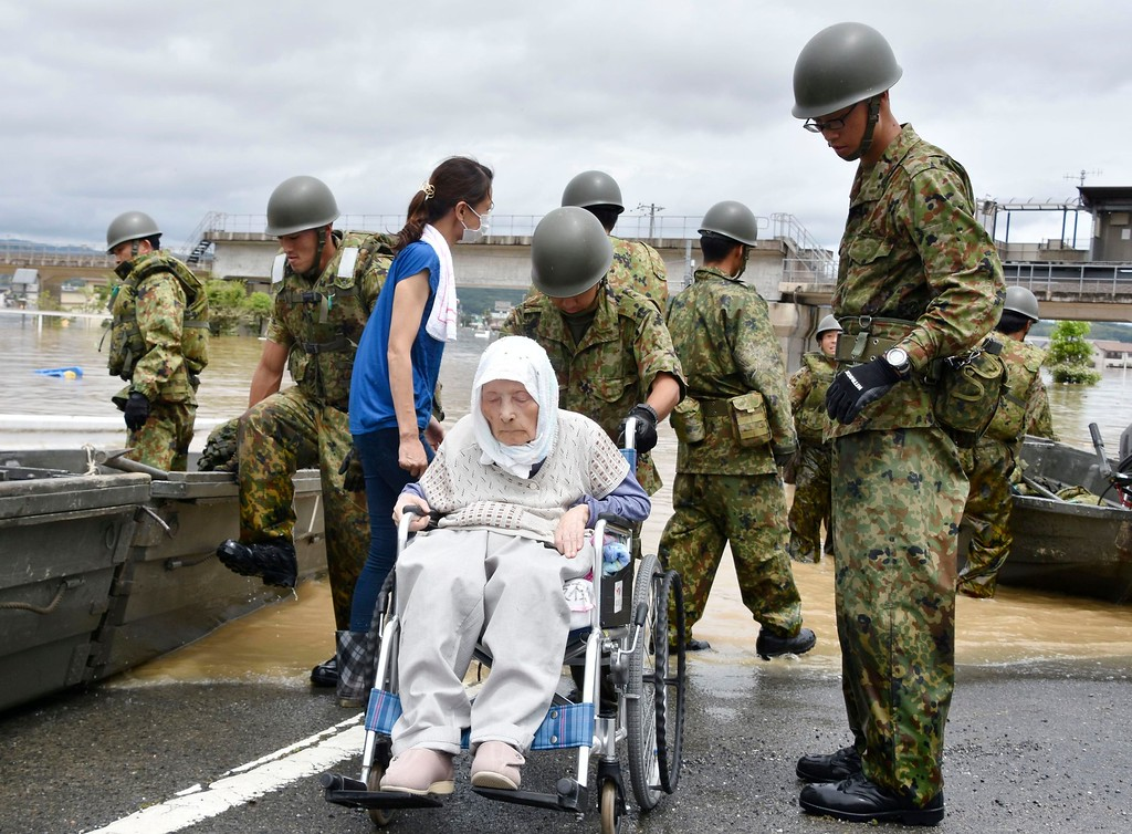 . Elderly people is rescued as the city is flooded following heavy rain in Kurashiki city, Okayama prefecture, southwestern Japan, Sunday, July 8, 2018. Heavy rainfall hammered southern Japan for the third day, prompting new disaster warnings on Kyushu and Shikoku islands on Sunday. (Kyodo News via AP)