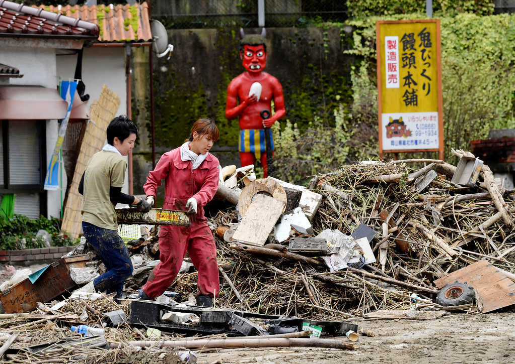 . Residents clean up near a house damaged by heavy rain in Soja city, Okayama prefecture, southwestern Japan, Sunday, July 8, 2018. Heavy rainfall hammered southern Japan for the third day, prompting new disaster warnings on Kyushu and Shikoku islands Sunday. (Koki Sengoku/Kyodo News via AP)