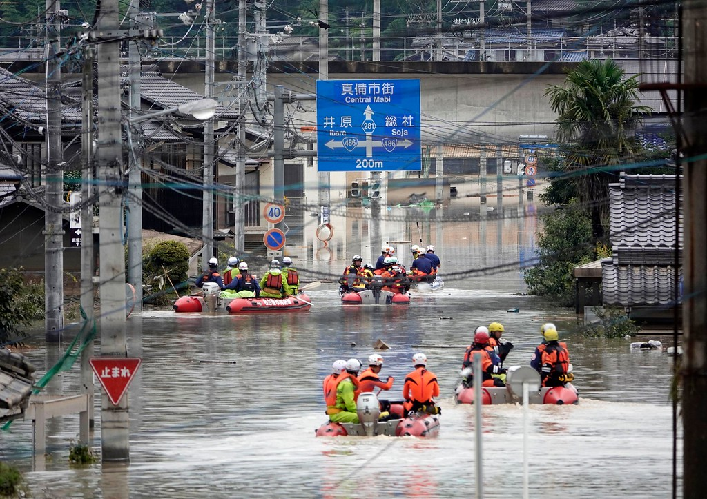 . Rescuers on boats head for search in the partly submerged area in water after heavy rain in Kurashiki city, Okayama prefecture, southwestern Japan, Sunday, July 8, 2018. Heavy rainfall hammered southern Japan for the third day, prompting new disaster warnings on Kyushu and Shikoku islands Sunday. (Koji Harada/Kyodo News via AP)