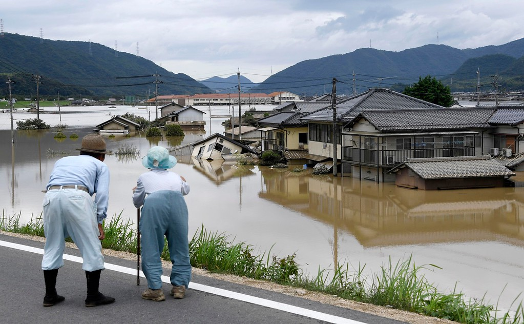 . Residents look at half submerged houses in floodwater from heavy rains, in Kurashiki, Okayama prefecture, southwestern Japan, Sunday, July 8, 2018. Heavy rainfall hammered southern Japan for the third day, prompting new disaster warnings on Kyushu and Shikoku islands Sunday. (Koji Harada/Kyodo News via AP)