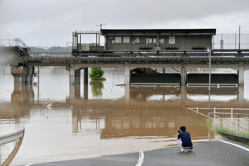 . A man uses smartphone at a flooded area near Kawabejuku train station after heavy rains in Kurashiki, Okayama prefecture, southwestern Japan, Saturday, July 7, 2018. Torrents of rainfall and flooding continued to batter southwestern Japan. (Koki Sengoku/Kyodo News via AP)