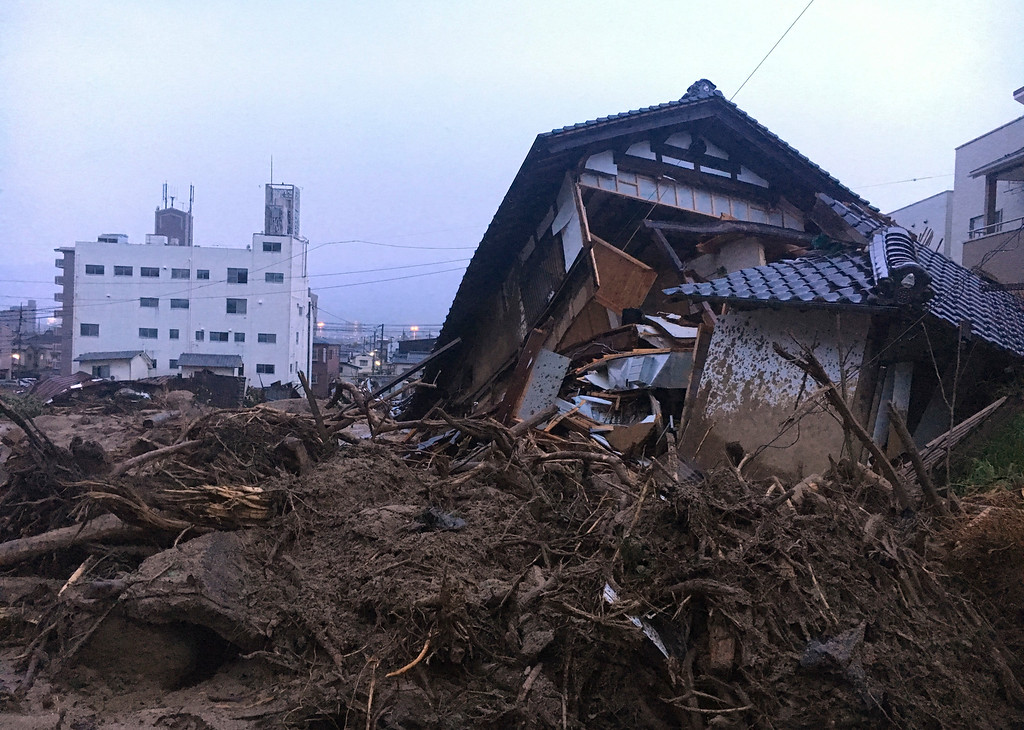 . Debris fills a small village following heavy rains Sunday, July 8, 2018, in Kuchita-Minami, Asakita-ku, Hiroshima, Japan. Searches continued Sunday night for dozens of victims still missing from the heavy rainfall that hammered southern Japan for the third straight day. (AP Photo Haruka Nuga)