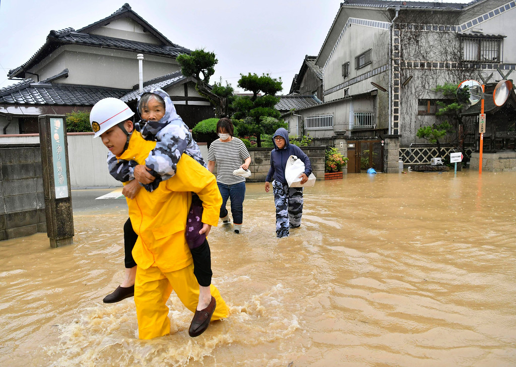 . Residents are evacuated to a safer place from floodwaters caused by heavy rains in Kurashiki, Okayama prefecture, southwestern Japan, Saturday, July 7, 2018. Torrents of rainfall and flooding continued to batter southwestern Japan. (Koki Sengoku/Kyodo News via AP)