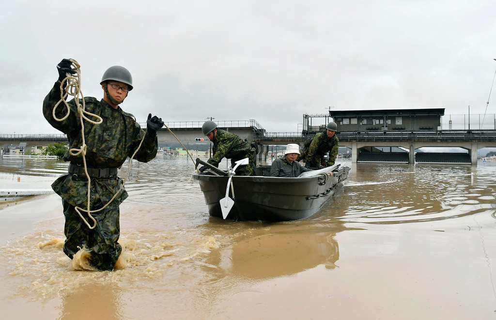. Japan Ground Self-Defense Force members use a boat to evacuate a resident from a flooded area caused by heavy rains in Kurashiki, Okayama prefecture, southwestern Japan, Saturday, July 7, 2018. Torrents of rainfall and flooding continued to batter southwestern Japan. (Koki Sengoku/Kyodo News via AP)