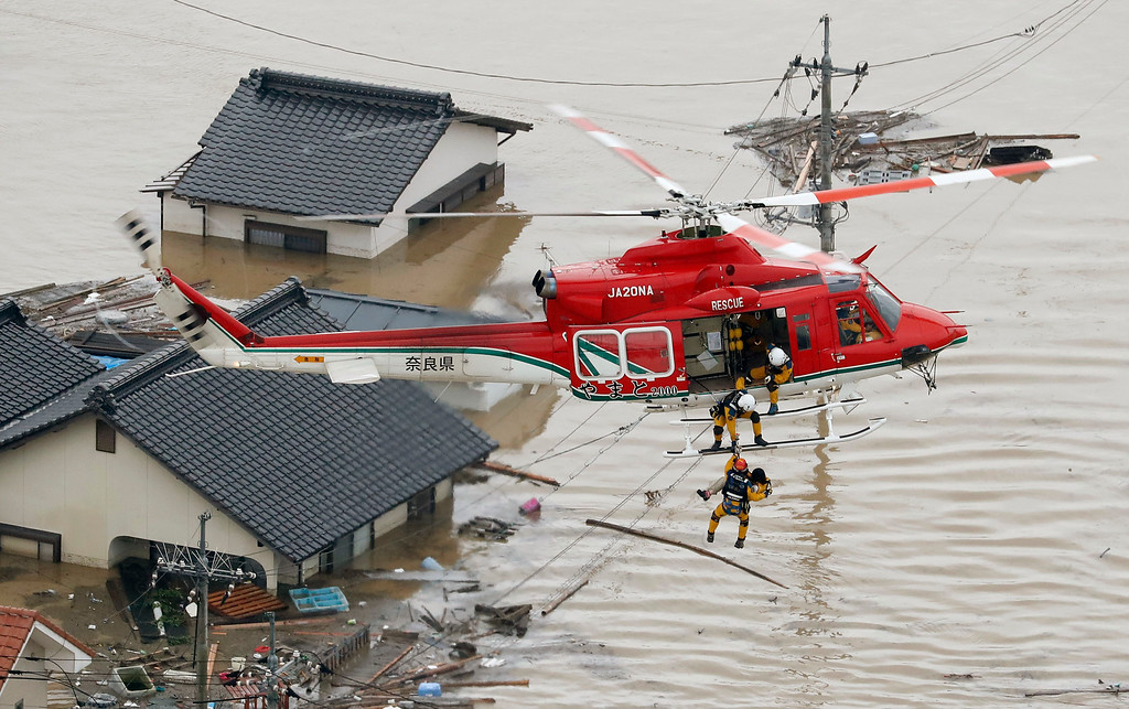 . In this July 7, 2018 photo, a resident is rescued in a flooded area in Kurashiki, Okayama prefecture, following heavy rain. Heavy rainfall hammered southern Japan for the third day, prompting new disaster warnings on Kyushu and Shikoku islands Sunday. (Shohei Miyano/Kyodo News via AP)