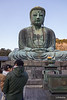The father held his daughter under the eyes of the Great Buddha, whose bronze statue was cast in the year 1252.