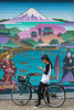 A young girl checking her cell phone in front of a mural in Asakusa, Tokyo, Japan.