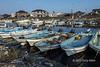 Line of skiffs with reflections and fishing parphenalia, Naruto Harbour, Shikoku Island, Japan