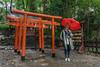 Woman-with-a-red-umbrella,-Torii-gates-and-ema-plaques,-Tosho-gu-Shinto-Shrine,-Shizuoka,-Japan