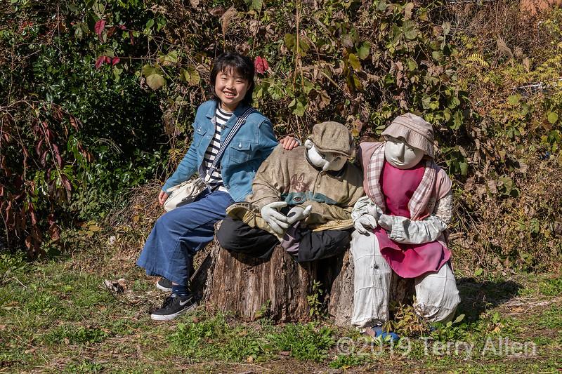 Japanes girl seated with kakashi, Nagoro Doll Village, Iya Valley, Japan