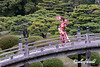 Young woman in beautiful kimono and obi on the Geishun-kyo Bridge, Ritsurin Garden, Takamatsu, Japan