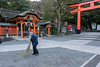 Custodian at Tamayama Inari shrine and entrance to the over 5000 torii gates, Fushimi Inari Taisha Shinto Shrine, Kyoto, Japan