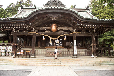 Yuko offering a prayer at the main shrine under a huge bell.