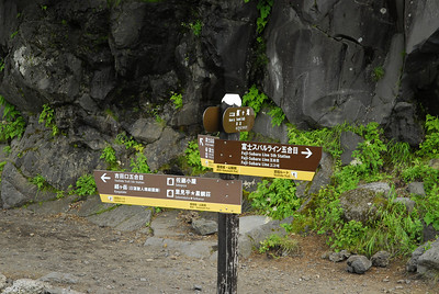 Sign post with choices on which way to go at the start of the accent at the entrance of the 5th station.
