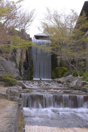 "This place is known as ""RYUMON NO TAKI"", one of the types based on TORYUMON, a legend of a carp which leaped up a waterfall and became a dragon. The waterfall is reconstructed by using rocks of Owari's suburban residence in Edo.  In 1669(Year 9 of the Kanbun period), Mitsutomo Tokugawa, the second generation domain lord, started construction of Owari's suburban residence(Toyama residence), which had the greatest garden of the day. In the garden, there was a RYUMON NO TAKI, framing the canyon named ""MEIHOUKEI"". The MEIHOUKEI had an elaborate device that caused the waterfall to swell when you crossed over all the steppingstones across the stream. All of the invited guests back in those days, generals(SHOGUN) and feudal lords(DAIMYO), were surprised and purred with pleasure.  The Toyama residence was located in Toyama town, Shinjuku ward, Tokyo. Although there is nothing much left to remind you of the Toyama residence nowadays, a large-scale rock garden from the Edo period was found on a premises of Waseda University in 1998(Year 10 of the Heisei period). Upon excavation by Waseda University and education board of Shinjuku ward, it was confirmed that the rock garden was a remains of the RYUMON NO TAKI in the Toyama residence. The stones were a volcanic rock called IZUISHI, with total number of 360 pieces and gross weight of 250 tons. It is presumed that they are a remainder of the building stones from the Edo castle. In Tokugawaen, these stones are used for bank protection, the riverbed, and stepping stones. They revived the RYUMON NO TAKI of Toyama residence by adopting the device of the swollen stream."