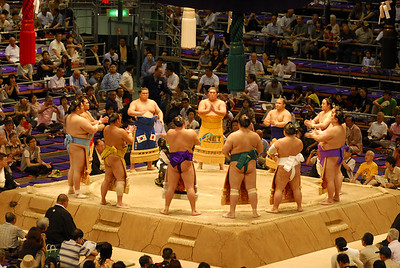 Sumo wrestlers gather in a circle around the gyoji (referee) in the dohyō-iri (ring-entering ceremony)