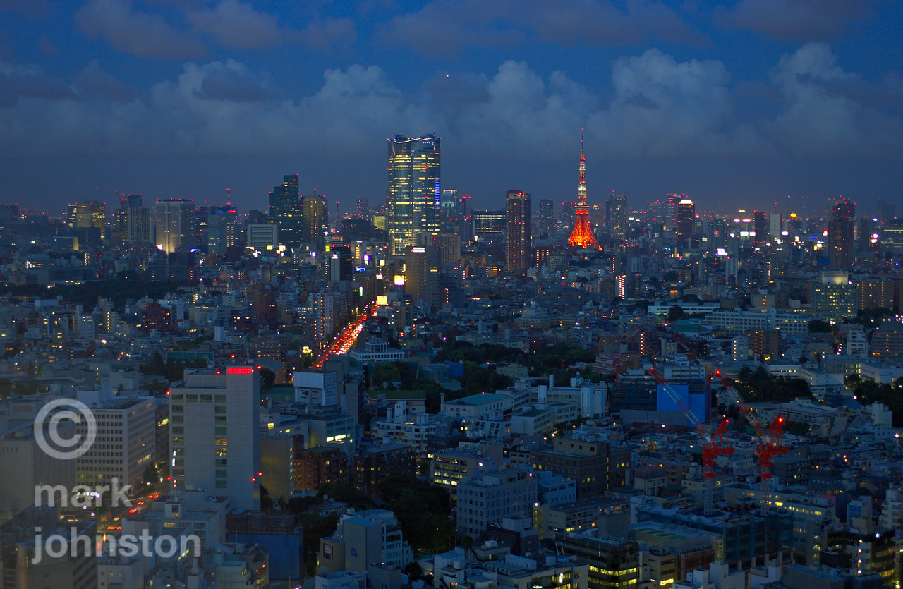 A fine summer evening descends on Tokyo.  Looking eastward from Shibuya, the two tallest structures visible are the massive Roppongi Hills complex, opened in April 2003 [54 stories/238 meters high], and Tokyo Tower, completed in 1958 [333 meters high - the tallest man-made structure in Japan].