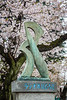 Cherry blossom trees and a Japanese sculpture in Ueno Onshi Park, Taito, Tokyo, Japan, Asia.
