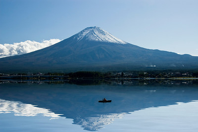 Fuji Mountain on a clear day, its reflection on the lake and fisherman on a boat. Kawaguchi, Japan