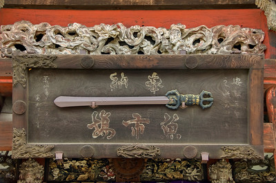 Display of a japanese sword hanging on a beautiful carved wood board outside a temple.Narita San near Tokyo, Japan.