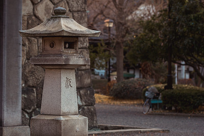 Japanese Stone Lantern in Front of a Temple Entrance with a Bicycle and Park in the Background (Translation: Revere/Contribute/Present)