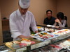 Making sushi at blistering speed in front of us.
