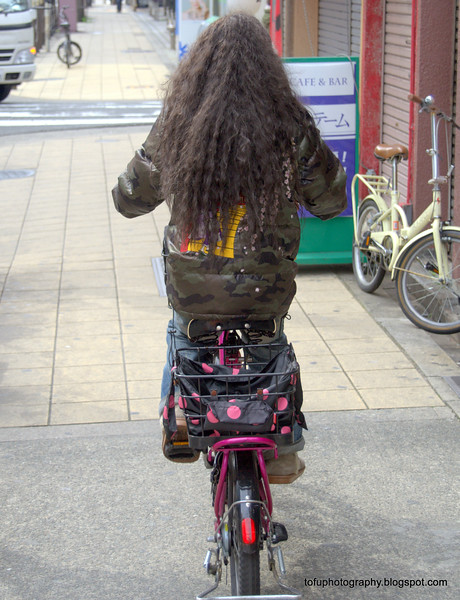 Woman with matted hair riding a bicycle in Osaka, Japan in March 2015