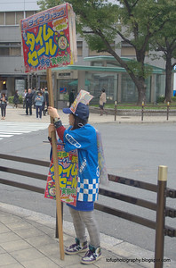 Woman advertising something in Osaka, Japan in March 2015