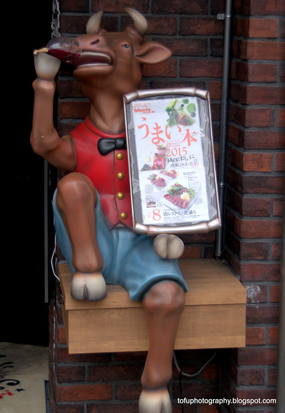 A  cow drinking wine and a restaurant menu outside a restaurant in Osaka, Japan in March 2015