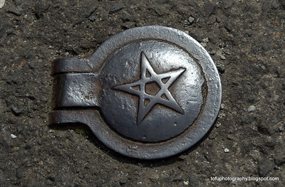 A metal  cover with a star on it in a road in Nagasaki, Japan in March 2015