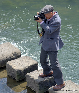 Man taking a photo while standing on a stone crossing in the Nagashima River in Nagasaki, Japan in March 2015