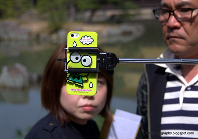 Woman having a selfie taken using a selfie stick at the Kinkakuji Temple in Kyoto, Japan in March 2015