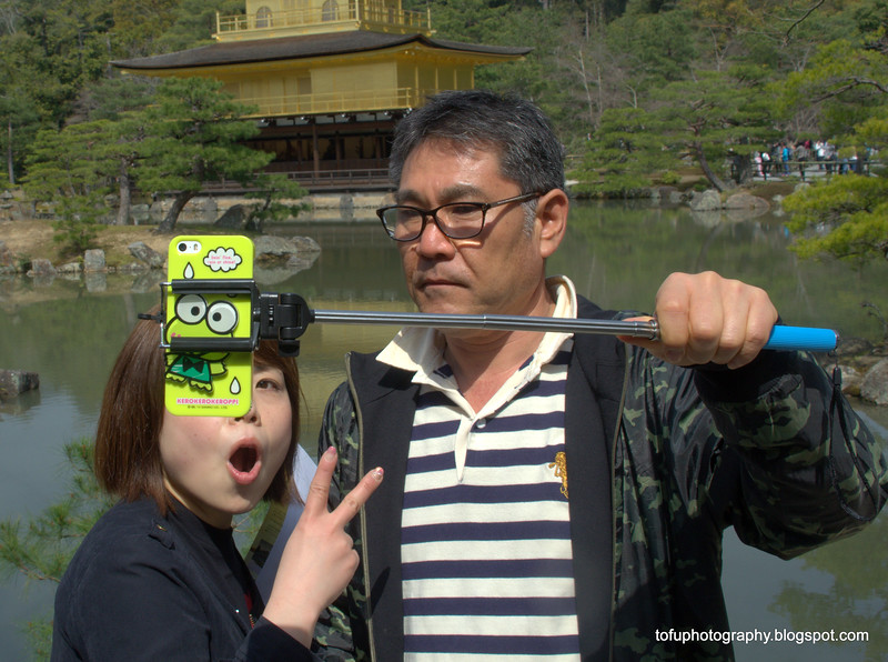 Woman having a selfie taken using a selfie stick at the Kinkakuji Temple in Kyoto, Japan in March 2015