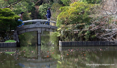 Woman crossing a bridge across the lake at Ryoanji Temple in Kyoto, Japan in March 2015