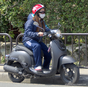 Woman on a black scooter in Kyoto, Japan in March 2015